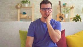 Retrato do homem novo com a dor de dente que senta-se no sofá