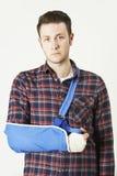 Retrato do homem novo com o braço no estilingue Imagens de Stock