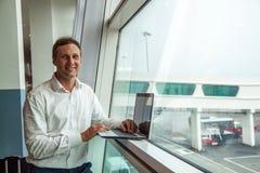 Retrato do homem novo considerável com um sorriso que verifica bilhetes planos na tabela contra a janela no aeroporto, espaço da  fotos de stock royalty free