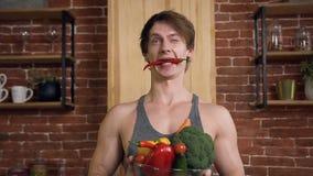 Retrato do homem novo considerável de sorriso com pimenta de pimentão em sua boca, estando atrás da mesa de cozinha e das terras  filme