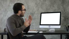 Retrato do homem novo considerável em ocasional no escritório que fala à câmera que explica algo perto da tela branco filme