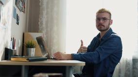 Retrato do homem novo considerável nos vidros com o polegar amarelo das mostras do cabelo na câmera Freelancer da casa que trabal video estoque
