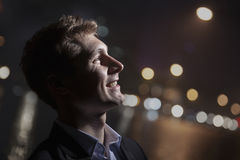 Retrato do homem novo de sorriso, perfil, luz brilhante que brilha na cara, tiro do estúdio Imagem de Stock