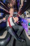Retrato do homem novo entusiasmado que guarda a flauta de champanhe quando mais gest Fotografia de Stock