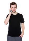 Retrato do homem novo feliz que fala no telefone celular isolado no wh Imagens de Stock Royalty Free