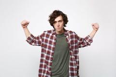 Retrato do homem novo forte na roupa ocasional que olha a câmera, mostrando o bíceps, músculos isolados no fundo branco da parede fotografia de stock