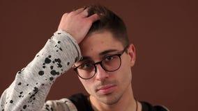 Retrato do homem novo moderno com vidros, leva sua mão através de seu cabelo vídeos de arquivo