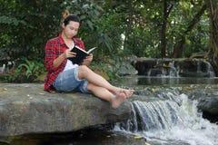 Retrato do homem novo do moderno na camisa vermelha que lê um livro no fundo bonito da natureza fotografia de stock royalty free