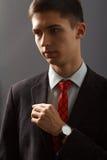 Retrato do homem novo no terno que mantém sua mão em sua caixa Foto de Stock Royalty Free