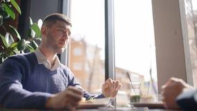 Retrato do homem novo que escuta seu sócio ao comer o café da manhã no café vídeos de arquivo