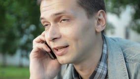 Retrato do homem novo que fala no telefone outdoor Árvore no campo Uma comunicação vídeos de arquivo