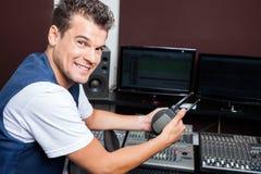 Retrato do homem novo que guarda fones de ouvido na tabela de mistura fotos de stock