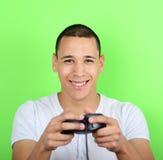 Retrato do homem novo que guarda o controlador do jogo e que joga jogos Fotografia de Stock Royalty Free