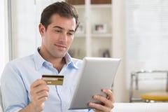 Retrato do homem novo que guarda o PC da tabuleta e o cartão de crédito Imagens de Stock Royalty Free