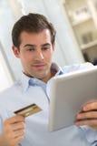 Retrato do homem novo que guarda o PC da tabuleta e o crédito card.indoor Imagens de Stock Royalty Free