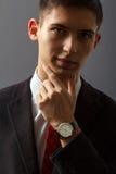 Retrato do homem novo que guarda seu queixo à mão com relógio de pulso Fotos de Stock
