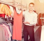 Retrato do homem novo que oferece às variações do vestido da amiga Fotografia de Stock