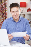 Retrato do homem novo que olha contas domésticas Foto de Stock