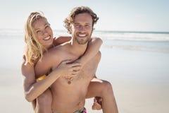 Retrato do homem novo que reboca a mulher bonita na praia Imagens de Stock Royalty Free