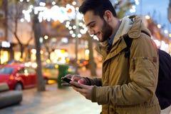 Retrato do homem novo que usa seu telefone celular na rua no ni Imagens de Stock Royalty Free