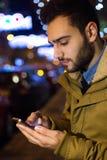 Retrato do homem novo que usa seu telefone celular na rua no ni Fotografia de Stock Royalty Free
