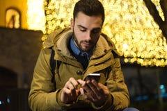 Retrato do homem novo que usa seu telefone celular na rua no ni Fotografia de Stock