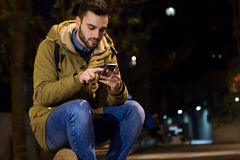 Retrato do homem novo que usa seu telefone celular na rua no ni Imagem de Stock Royalty Free