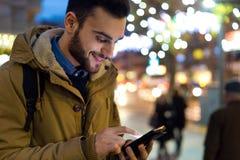 Retrato do homem novo que usa seu telefone celular na rua no ni Imagens de Stock