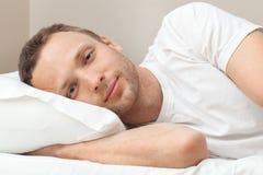 Retrato do homem novo satisfeito na cama Foto de Stock