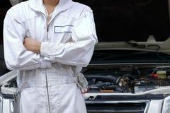 Retrato do homem novo seguro do mecânico no uniforme com braços cruzados e da posição contra o carro na capa aberta na garagem do Imagem de Stock Royalty Free