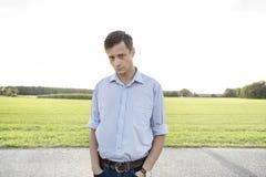 Retrato do homem novo triste com mãos em uns bolsos que estão na estrada rural Imagem de Stock