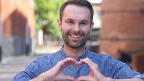 Retrato do homem ocasional de sorriso que gesticula o coração com mão vídeos de arquivo