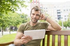 Retrato do homem ocasional de sorriso que olha o tablet pc no st fotografia de stock royalty free