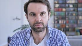 Retrato do homem ocasional sério da barba que olha a câmera vídeos de arquivo