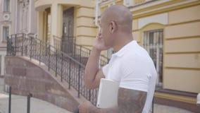 Retrato do homem do Oriente Médio calvo seguro bem sucedido considerável que fala pela posição do telefone celular na rua dentro filme