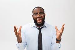 Retrato do homem preto irritado desesperado que grita na raiva e na raiva que rasgam seu cabelo para fora ao sentir furioso e lou imagem de stock