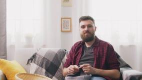 Retrato do homem que senta-se no sofá e que faz malha em casa filme