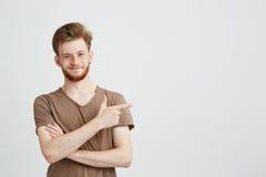 Retrato do homem sincero considerável novo com barba que sorri olhando a câmera que aponta o dedo no lado sobre o branco Fotos de Stock Royalty Free