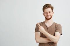 Retrato do homem sincero considerável novo com barba que sorri olhando a câmera que aponta o dedo no lado sobre o branco Foto de Stock