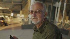 Retrato do homem superior com cabelo cinzento e a barba cinzenta exteriores no fundo da cidade video estoque