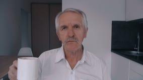 Retrato do homem superior com café bebendo do bigode em casa na cozinha na manhã filme