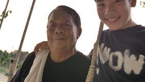 Retrato do homem superior e do menino novo com cara do sorriso, 4K Handheld do menino asiático com o pai grande no balanço que ol video estoque