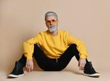 Retrato do homem superior do milionário do cabelo cinzento em óculos de sol amarelos que aponta os dedos acima imagens de stock