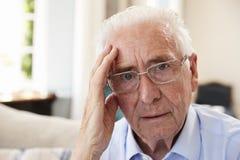 Retrato do homem superior que senta-se em Sofa Suffering From Depression fotografia de stock