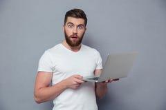 Retrato do homem surpreendido que guarda o laptop Foto de Stock Royalty Free