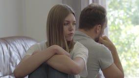 Retrato do homem triste e da mulher que sentam-se de volta à parte traseira com caras infelizes em casa Problemas no relacionamen vídeos de arquivo