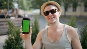 Retrato do homem do viajante que guarda o telefone esperto com o chromakey verde da tela, olhando a câmera e o sorriso video estoque