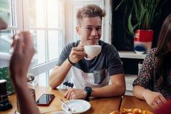 Retrato do indivíduo novo à moda que guarda um copo do chá que come o café da manhã com os amigos no café imagem de stock royalty free