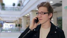 Retrato do indivíduo novo elegante com vidros em um shopping com um telefone vídeos de arquivo