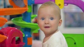 Retrato do infante feliz bonito na sala de jogo em fundo unfocused filme